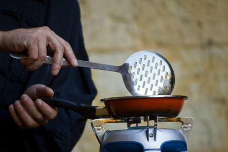 Chef cooking into a pan photo