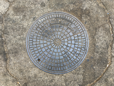 City of Los Angeles manhole cover on cement pavement