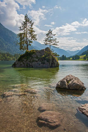 Fir trees on a small rocky island lake Hintersee Bavaria