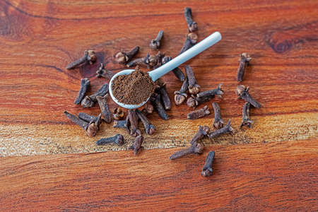 Cloves whole and ground on a wooden cutting board