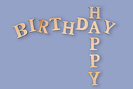 Happy birthday written in wooden letters on blue background