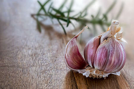 Garlic bulb with a twig of rosemary on wooden board
