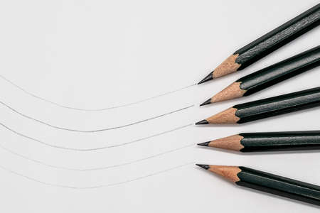 Five pencils with different degrees of hardness and sample line on paper Фото со стока