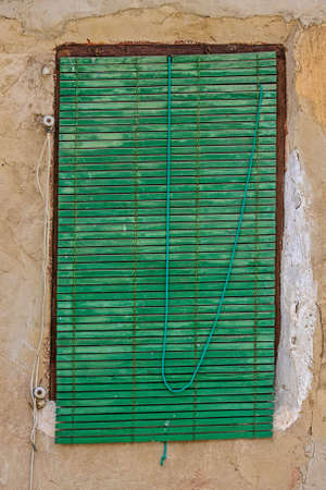 Old green window shutters and ocher colored house wall