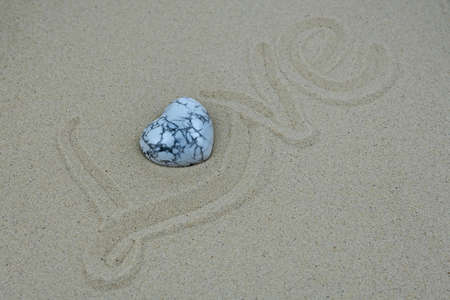 Love written in the sand with a heart-shaped marble stone