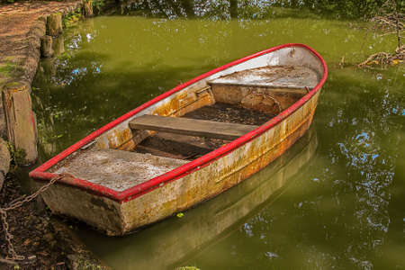 Old weathered rowboat in a pond