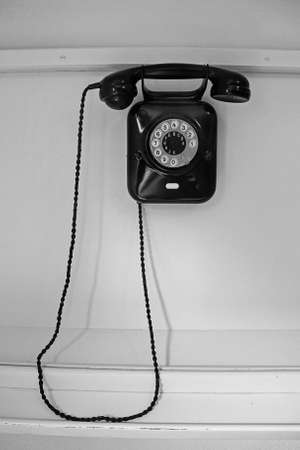Old fashioned black wall phone on white wall