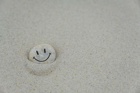 Pebble with smiley face on it lying in the sand