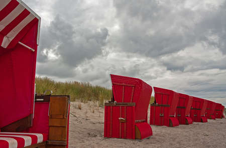 End of the holiday season, a row of beach chairs, all but one facing away from the sea