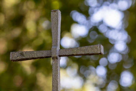 Old weathered christian cross in the back green and light-filled bubbles Stockfoto