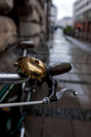 Close up of a brass bell on a bicycle parked in a street in Munich on a rainy day