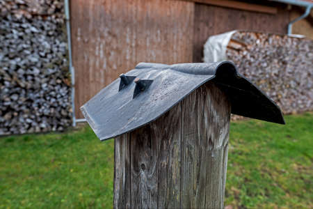 Plastic cover on a wooden fence post, protection against rain and snow Stockfoto
