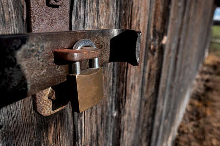 Close-up of an old door lock with modern padlock on a barn