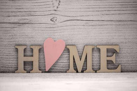 the word home in wooden letters in front of a wooden background, the O is a wooden pink heart