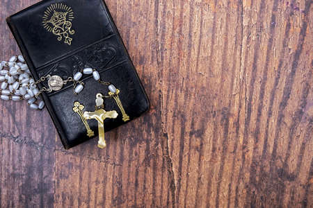 old leather-bound prayer book with gold embossing and art nouveau floral pattern and old rosary with ivory cross Stock Photo