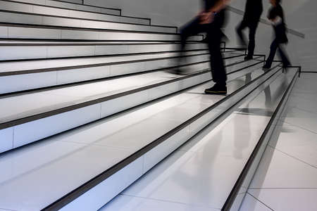 white black staircase in a building with hurrying people narrow focus on the shoes