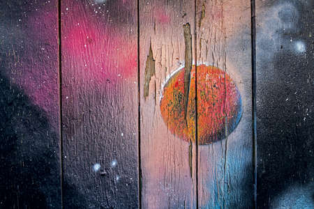 maybe a sprayed sunrise, sunddown or galaxy on a old wooden wall Stockfoto