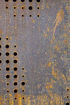 rusted originally black colored metal with circular holes Stockfoto