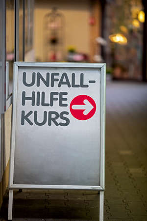 Sign with silver-colored frame with red arrow pointing the way to the location of the first aid course, text in german language Unfall Hilfe Kurs, translated first aid class