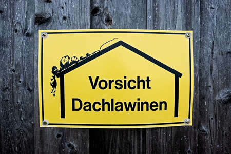warning sign with a simple drawing of a house and a roof avalanche, with the German inscription Caution Roof Avalanches in english be careful roof avalanches