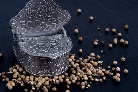 Whole and crushed peppercorns lying around a pewter storage jar on a slate plate Stockfoto