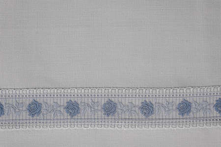 Embroidered border with roses in blue white on a white cotton table cloth Imagens