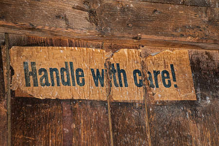 old torn paper sticker with text in block letters, Handle with care, glued to an old wooden box