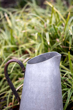 upper part of an old metal jar used for watering plants, in front of grass