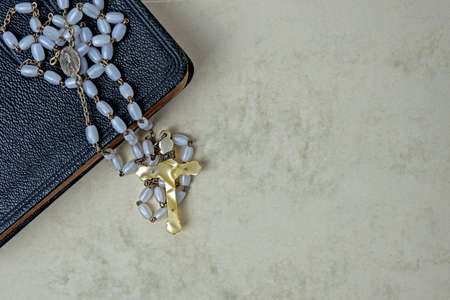 rosary with with beads and ivory cross on black leather bound prayer book Stock Photo