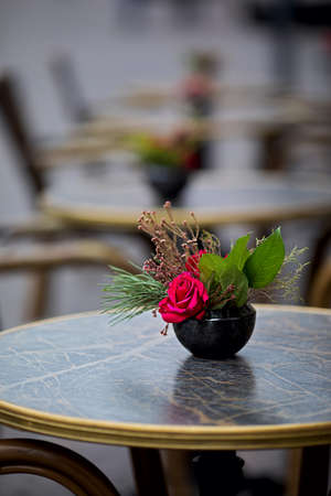 red roses with leaves in ceramic flower pot on restaurant tables