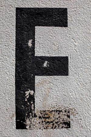 capital letter E painted on a house wall with chipped paint Reklamní fotografie