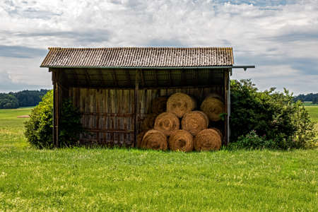 Typical wooden hut in Bavarian fields to protect feed and animals Stok Fotoğraf
