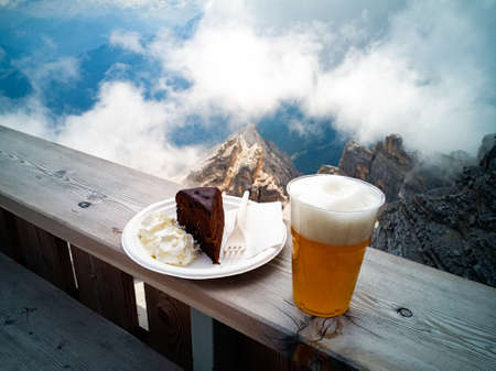 Blond beer and a slice of Sachertorte, mountains, rocks and clouds on the background Stock Photo - 105871578