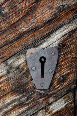 Ancient door locker in an old, carved wood door Stock Photo