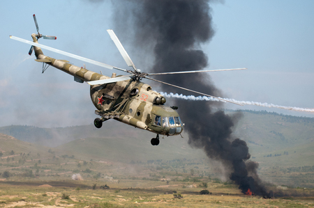 explosion engine: Buryatia, Russia - August 17, 2012: Military training.Helicopters mounting a ground attack with explosions and smoke