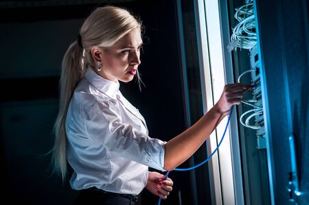 service engineer: Young engineer businesswoman in network server room. Russia. Stock Photo
