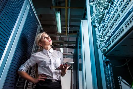 Jeune femme d'affaires ingénieur dans la salle de serveur réseau. Russie.