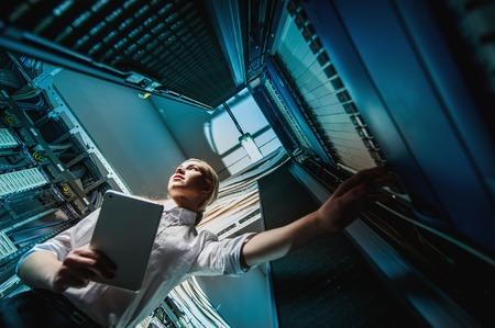 gerente: empresaria joven ingeniero en la sala de servidores de red. Rusia.