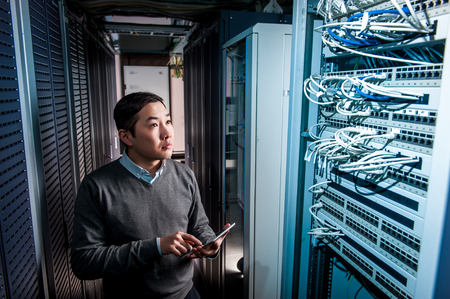 database server: Young engineer businessman in network server room