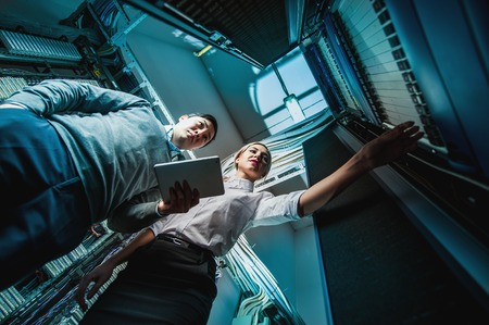 database server: Young engineers businessmen in network server room Stock Photo