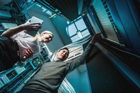 若いエンジニアは、ネットワーク サーバー ルームのビジネスマン 写真素材