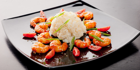 exotically: rise with shrimps on the black dish on the wooden table