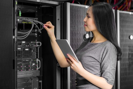 database server: Young engineer businesswoman with tablet in network server room