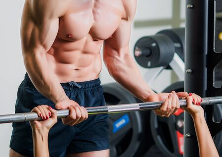male muscle: sport, fitness, teamwork, weightlifting and people concept - personal trainer with barbell flexing muscles in gym