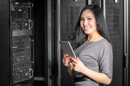 computer tech: Young engineer businesswoman with tablet in network server room