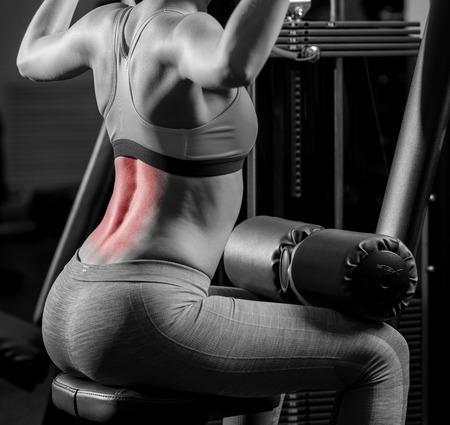 osteoporosis: Mujer que ejercita en el club deportivo y tiene dolor de espalda