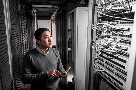 security room: Young engineer businessman in network server room
