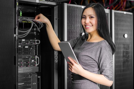 Young engineer businesswoman with tablet in network server room Imagens - 51764083