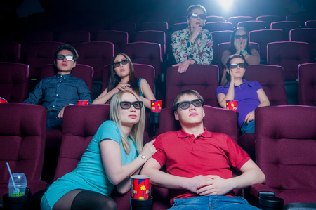 enjoymant: People in the cinema wearing 3d glasses and watching movie