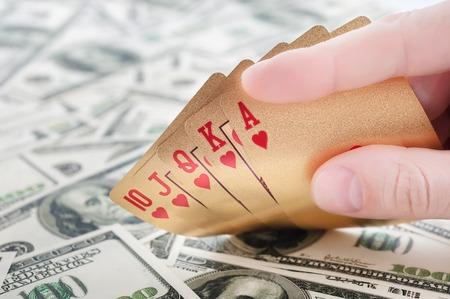 jack pot: Gold poker cards on money background on a table